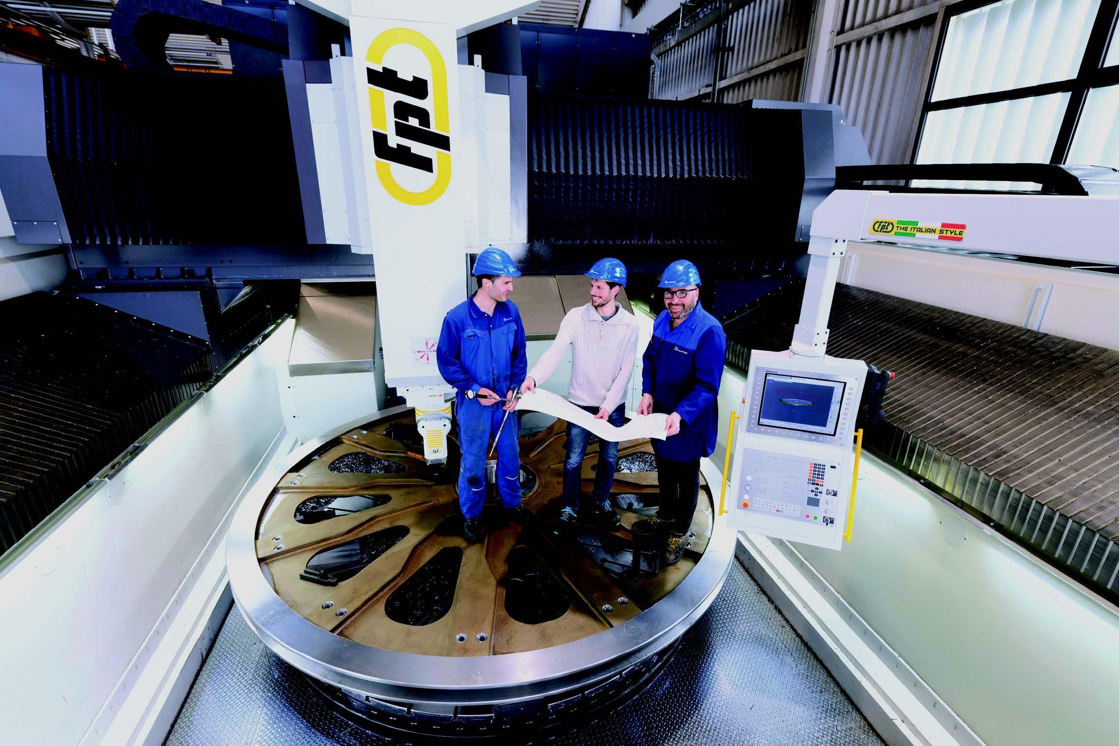 Das Foto mit Christof Karlegger (links), Ing. Peter Plattner (Mitte) und Franz Frei (rechts) beim Einrichten der gewaltigen Seilscheibe für den Flughafen London-Luton zeigt, wie viel Raum es in der Maschine für große Projekte gibt.